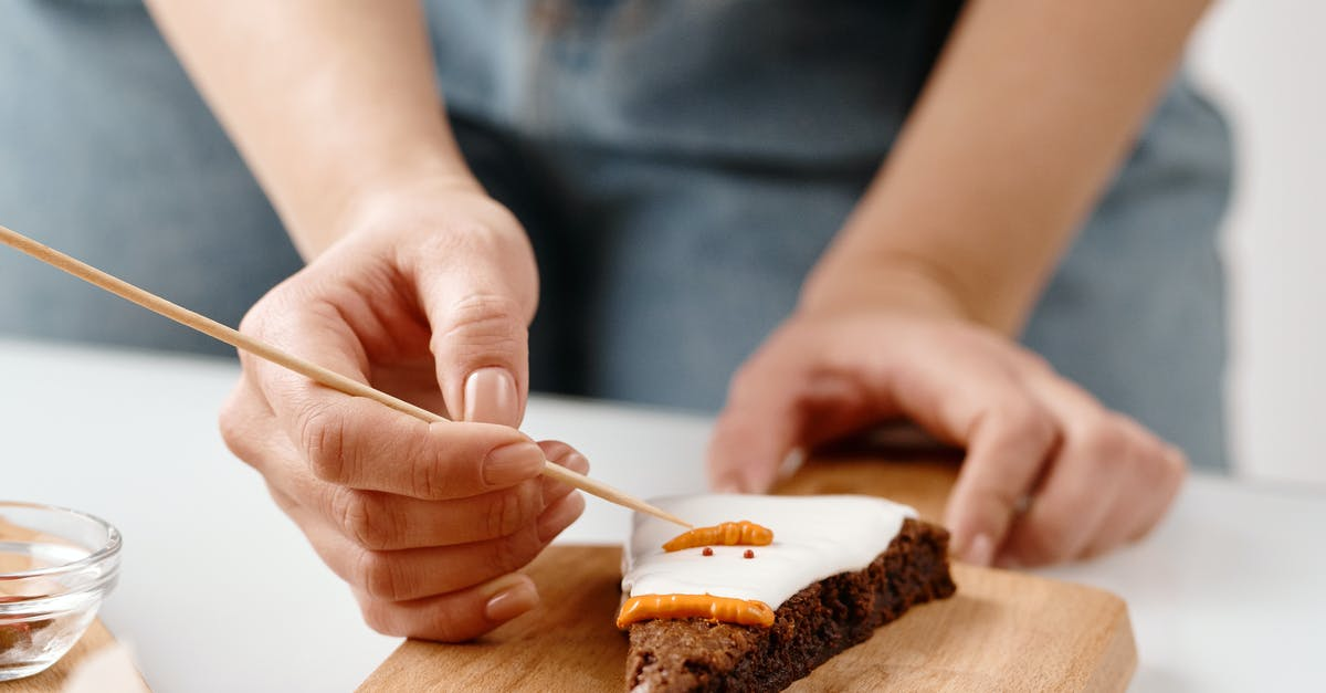 A close up of a person cutting a piece of cake on a plate